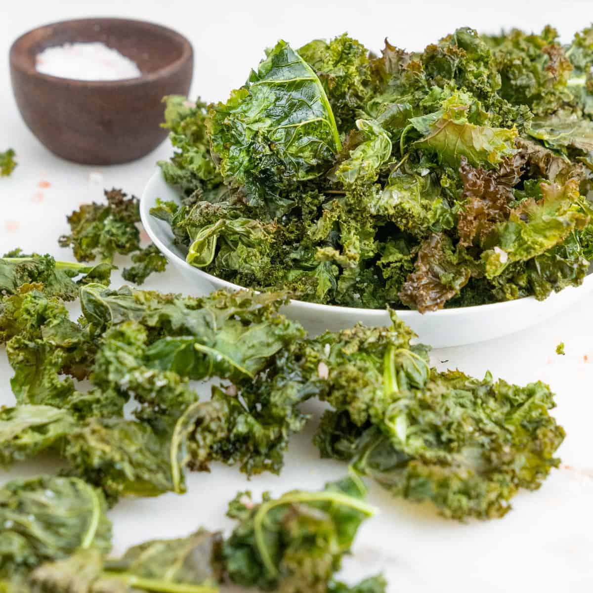 Crispy Baked Kale Chips spread out on a white surface and in a bowl with a bowl of salt in the background
