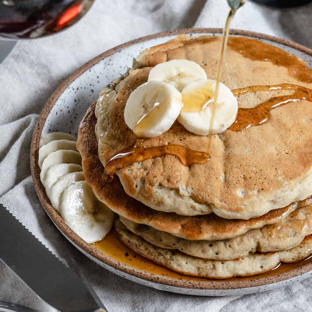 completed stack of banana pancakes on a white plate with bananas and maple syrup on top