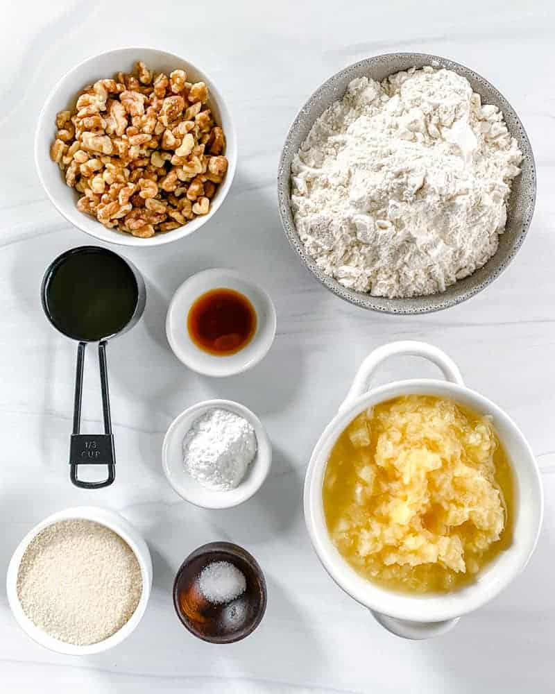 Pineapple Walnut Muffins ingredients in several white bowls on a white background