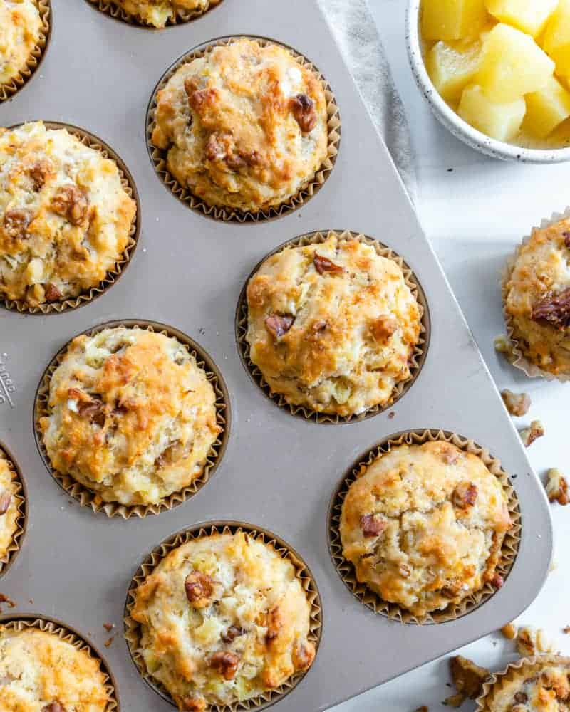 several Pineapple Walnut Muffins in a muffin pan with ingredients in the background