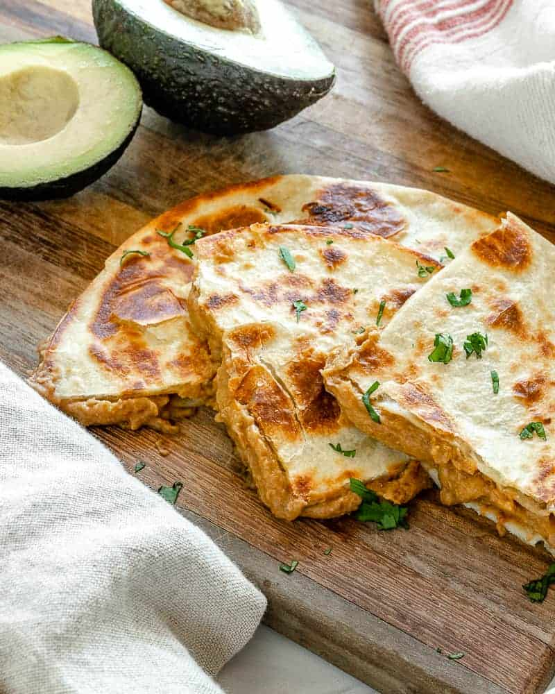 finished vegan bean quesadilla on a wooden board with ingredients in the background
