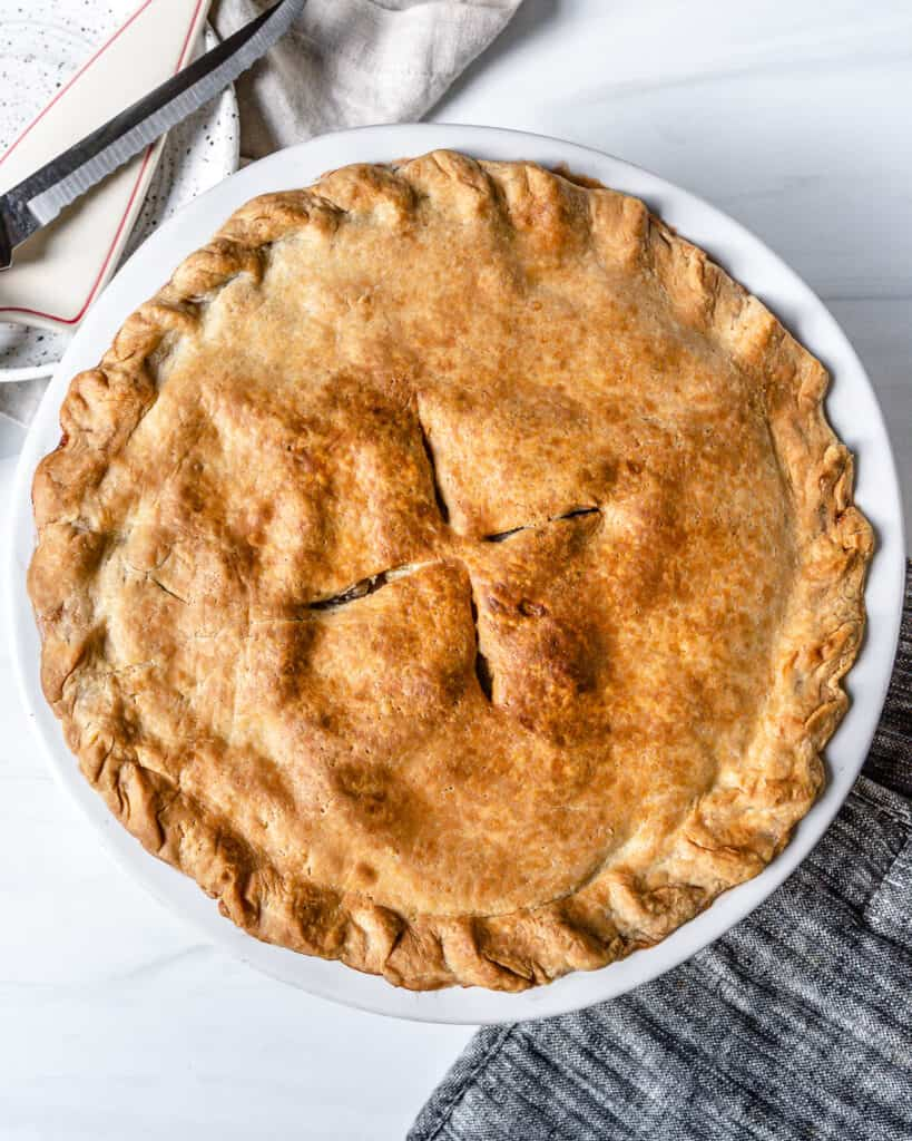 completed apple pie in a white circular pan against a white background