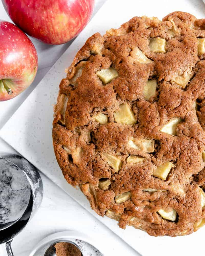 finished apple cake with two apples and measuring tools against a white background