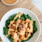 completed bowl of tofu with peanut sauce in white bowl against light brown background