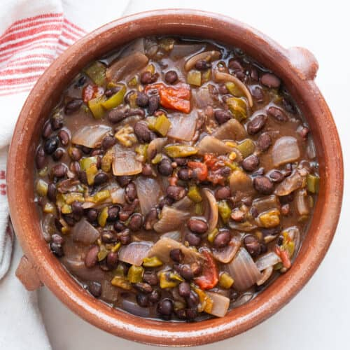 finished black bean chili in brown bowl against a white background