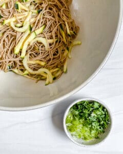 white bowl of soba noodles and cucumber and another bowl of green veggies/herbs against white surface