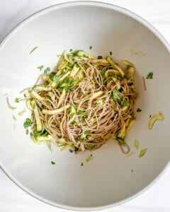 mixed bowl of soba noodles with cucumbers mixed with green veggies and herbs