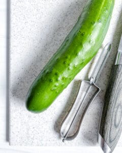 process for Soba Salad with Sunomono-Style Cucumbers with cucumbers and knife on cutting board