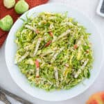 completed brussels sprouts slaw in a white bowl with brussels sprouts in the background