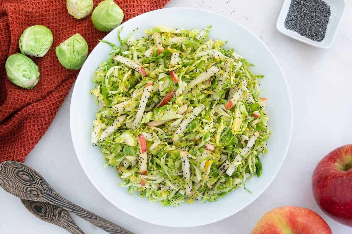 Brussels Sprouts Slaw in a white bowl  with apples and brussels sprouts on the side