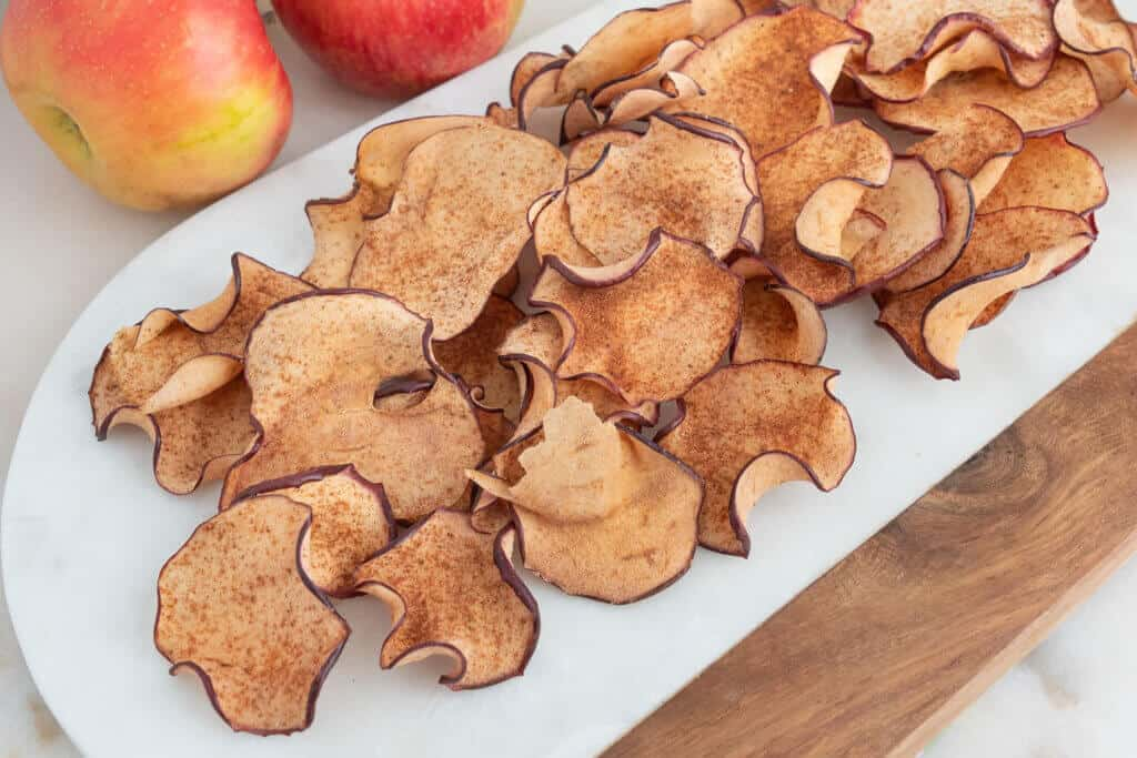 finished apple chips spread out on a white tray
