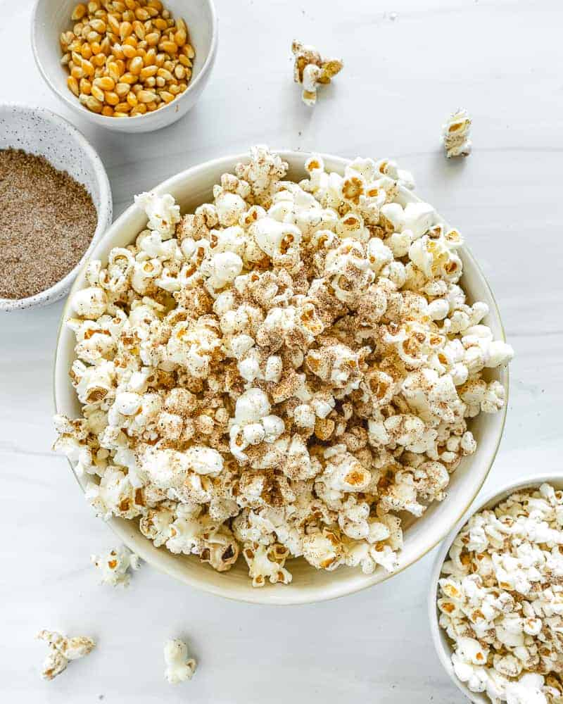 chai popcorn in a big and small bowl with seasonings in the background