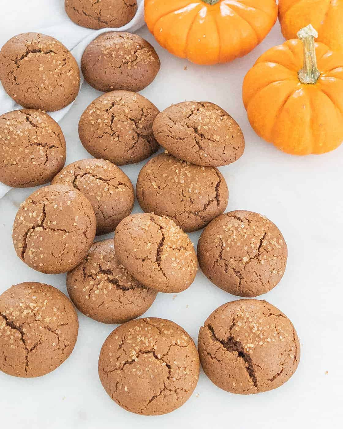 several pumpkin molasses cookies with pumpkin in the background against a white surface