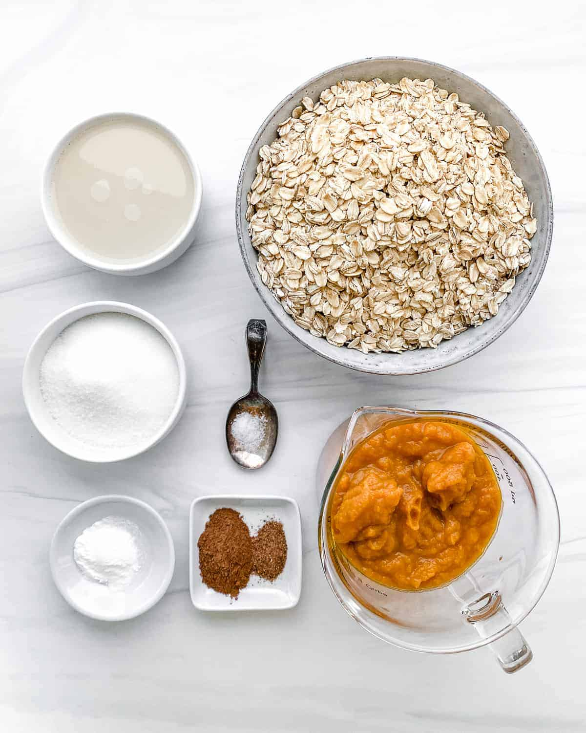 ingredients for pumpkin oatmeal cookies against a white marble surface