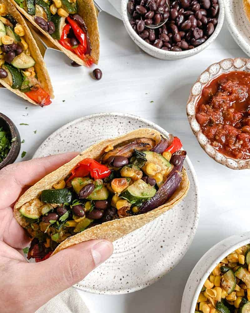 Vegan Roasted Veggie Tacos in a white plate with ingredients in the background against a white surface