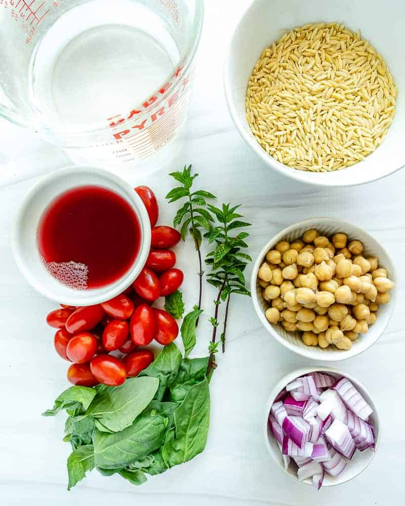 uncooked orzo chickpea salad ingredients measured out against a white surface