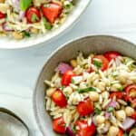 finished orzo chickpea salad in a white bowl with ingredients on a white background