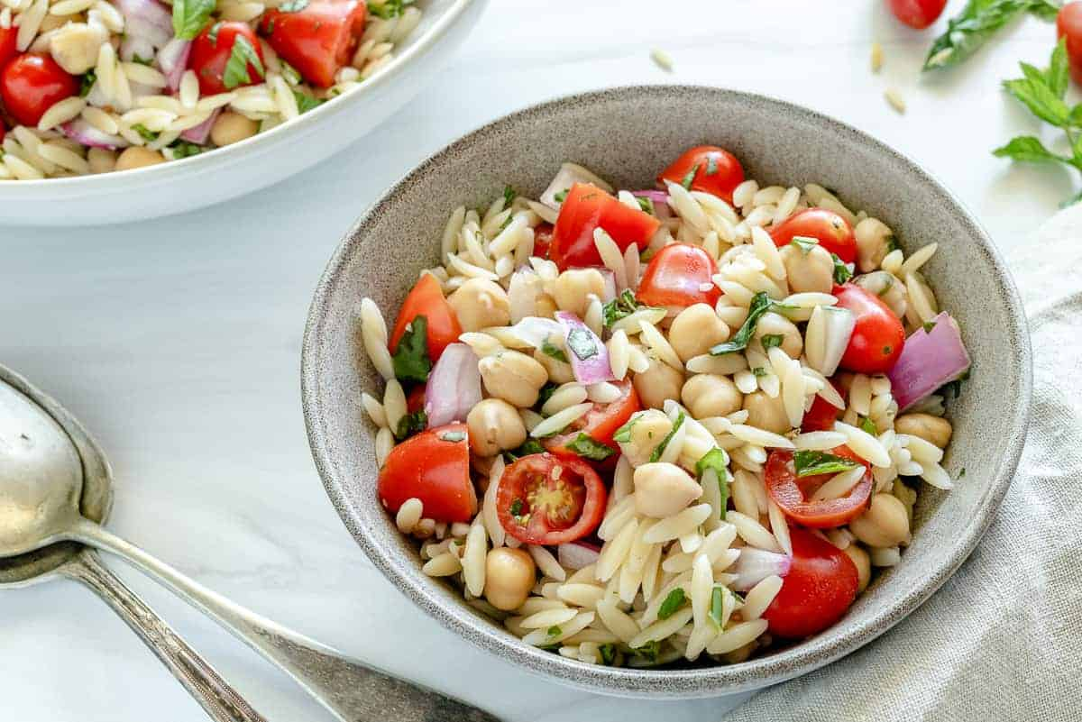 finished orzo chickpea salad in a white bowl with ingredients in a white background