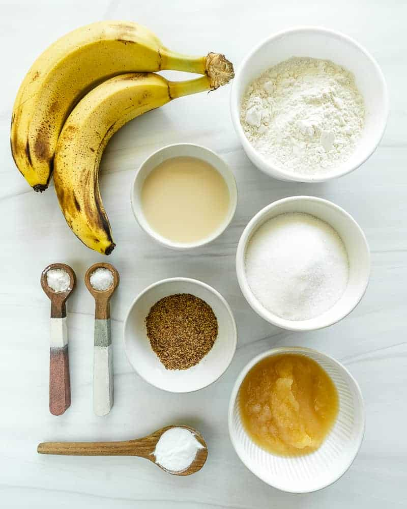 Oil-Free Banana Muffins ingredients in white bowls on white surface