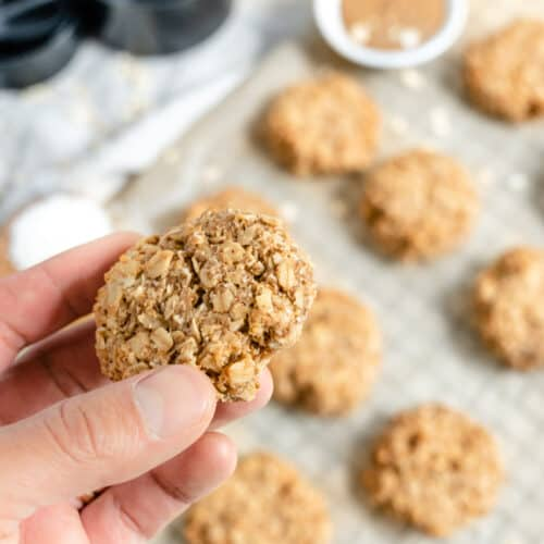 close up of Coconut Oatmeal Cookie with several cookies on a gray baking tray with ingredients in the background
