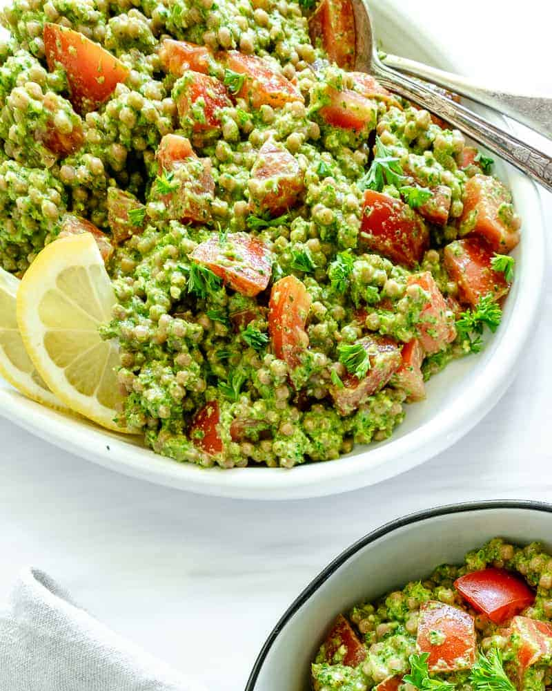two bowls of arugula pesto couscous in a white platter and bowl against a white background