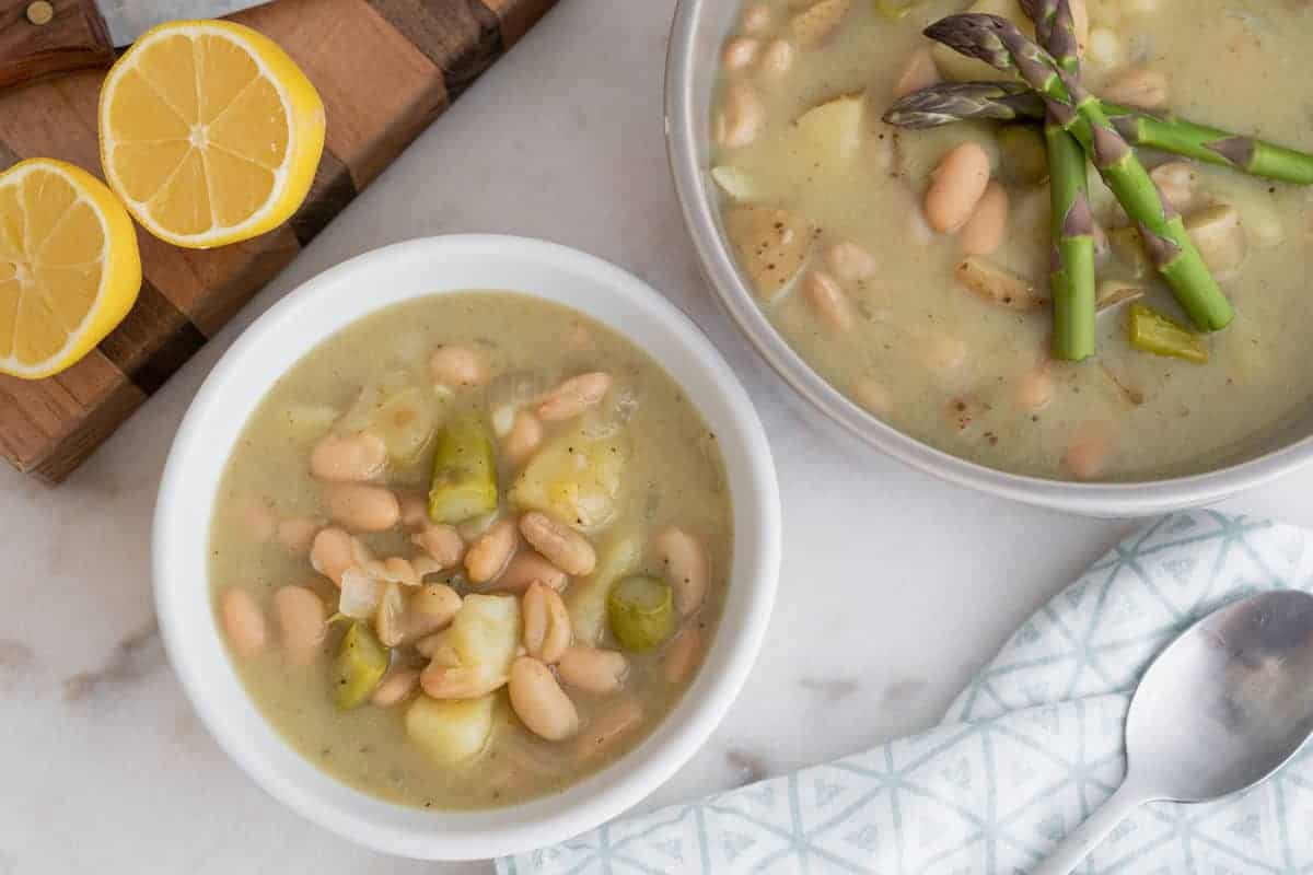 finished creamy asparagus soup separated into two bowls against a white background with lemon on the side