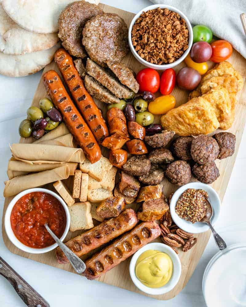 variety of plant based meats on a platter in a white background