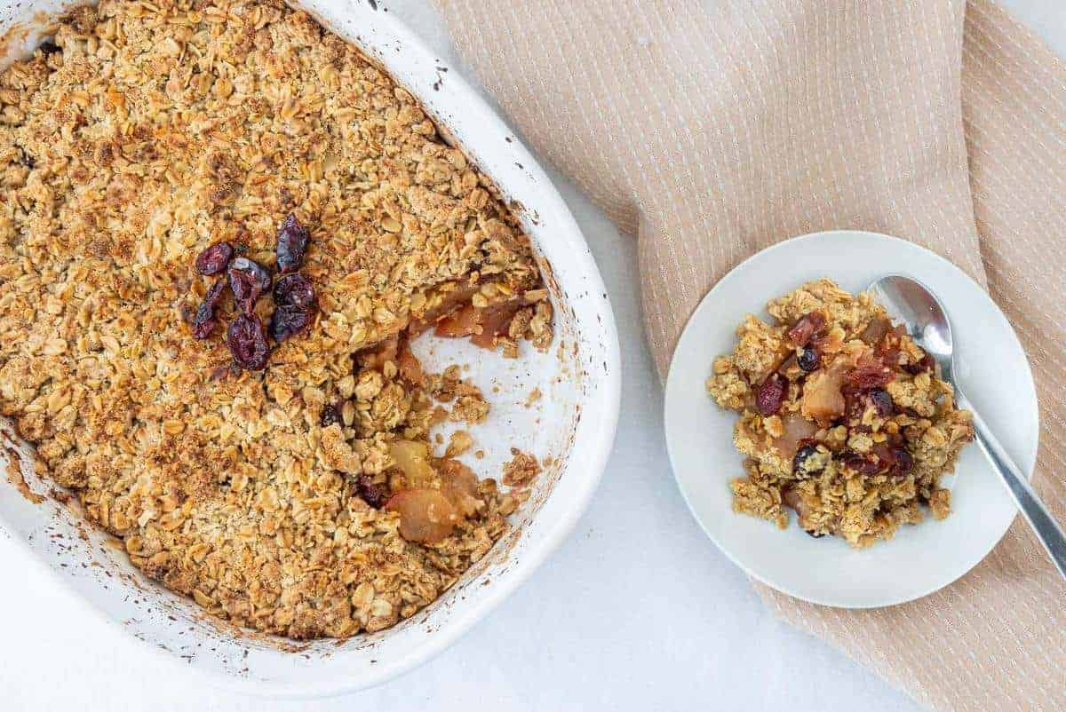 apple cranberry crisp with a piece put on a white plate