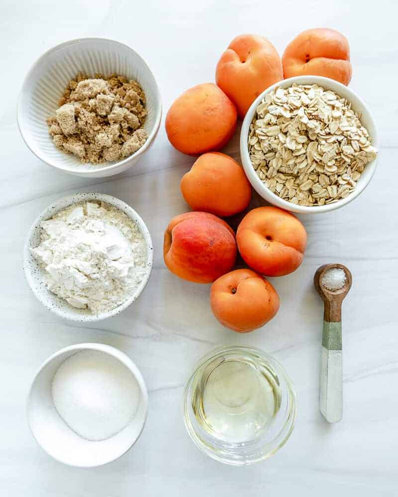 six peaches with a white cup of oats, sugar, flour, and a measuring spoon
