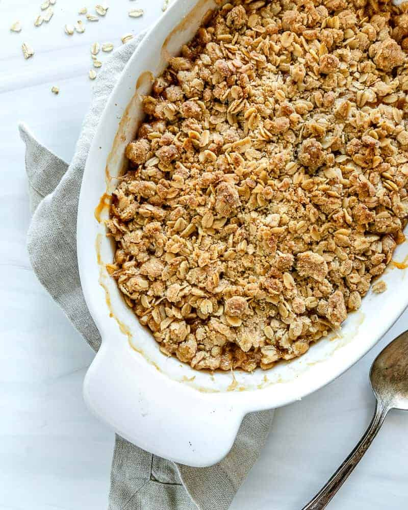 one white bowl of apricot crisp with a white background