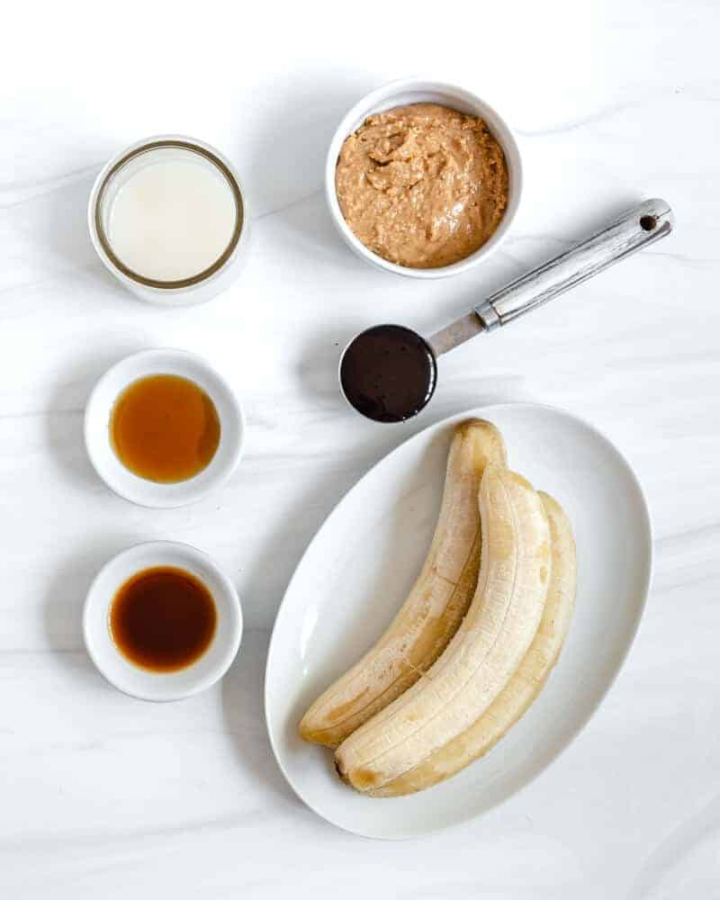 two frozen bananas in a white dish, a small bowl with vanilla extract, a small bowl with maple syrup and a small jar with plant milk and a medium bowl with peanut butter