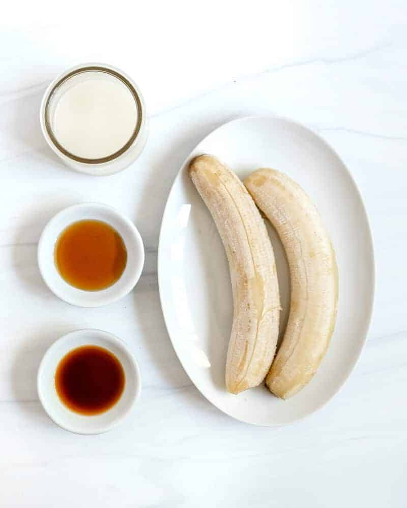 two frozen bananas in a white dish, a small bowl with vanilla extract, a small bowl with maple syrup and a small jar with plant milk