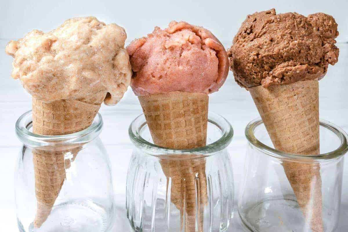 Three cones in clear jars, each with a scoop of strawberry banana ice cream, chocolate PB ice cream and simple banana ice cream