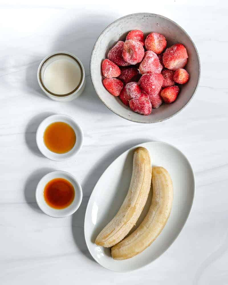 two frozen bananas in a white dish, a small bowl with vanilla extract, a small bowl with maple syrup and a small jar with plant milk and a big bowl of frozen strawberries