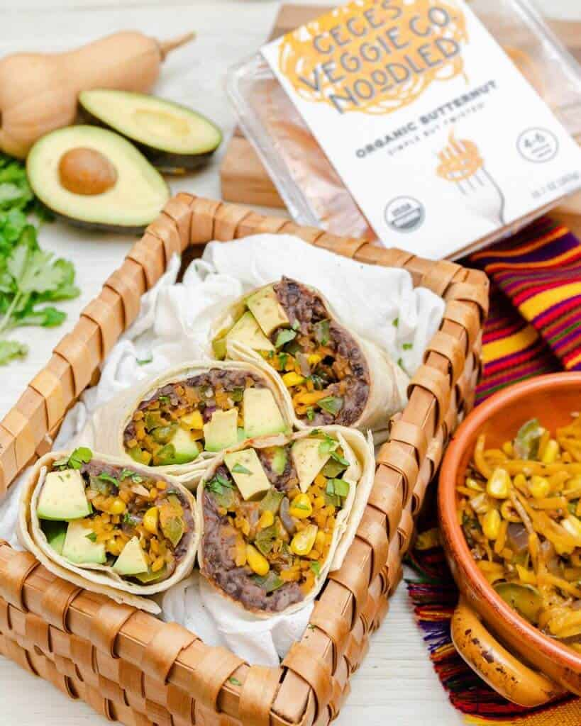 Butternut Squash Burritos in a basket with several ingredients in the background