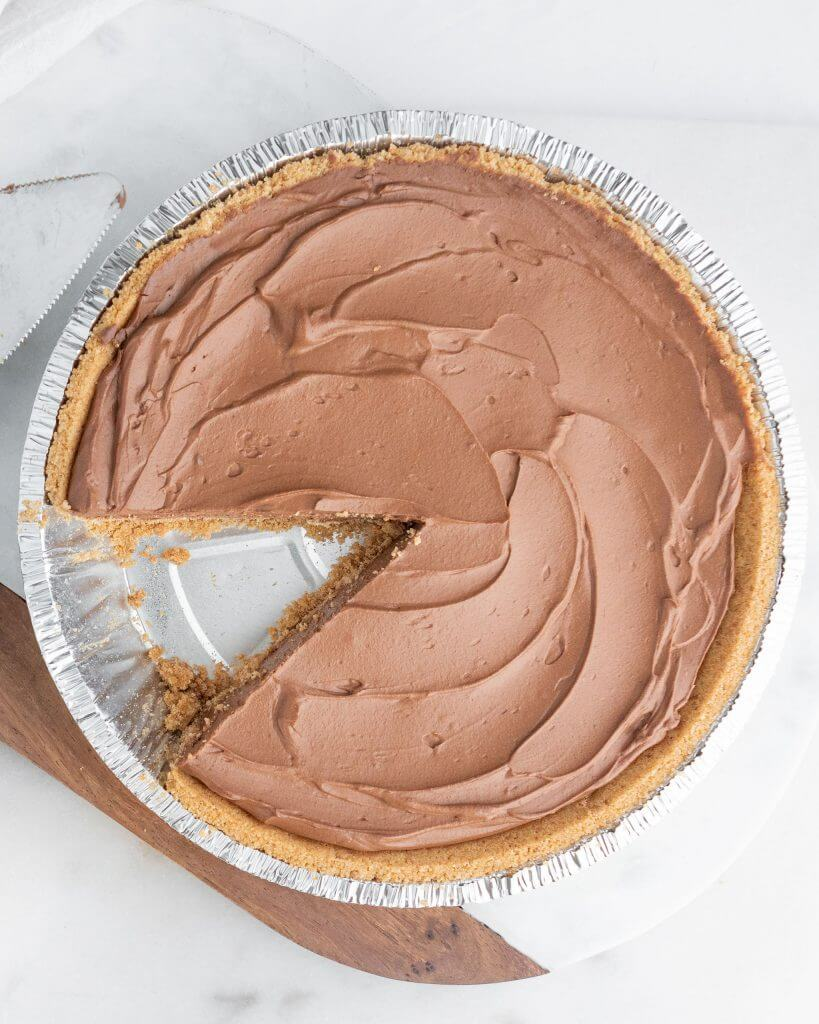Vegan chocolate pie with one slice cut out. It's in an aluminum pie tin, on top of white and wood cutting board.