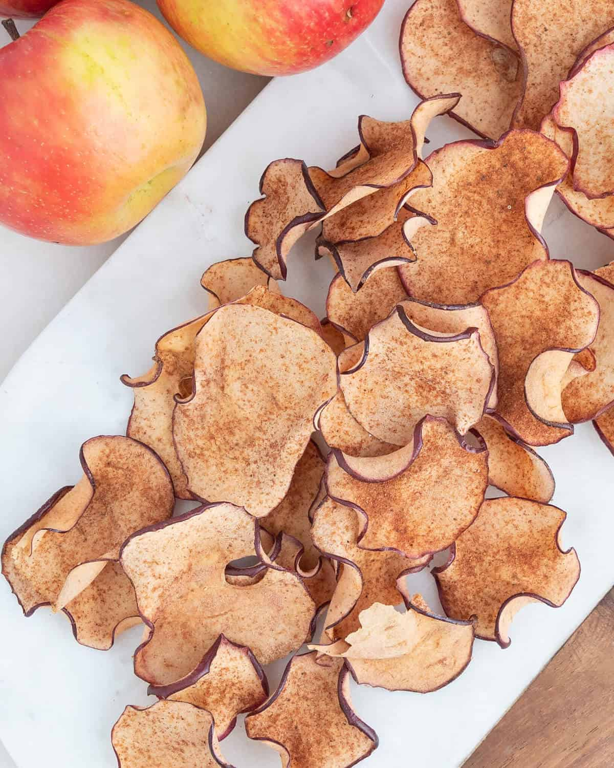 several crispy apple chips on a white platter with apples in the background