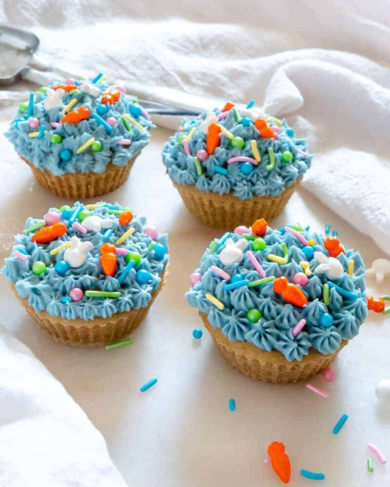 4 Depression Era Vanilla Cupcakes with blue frosting and sprinkles on a white background