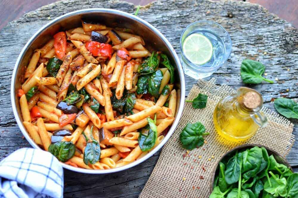 finished Eggplant Penne in a dish with ingredients spread out against a dark background