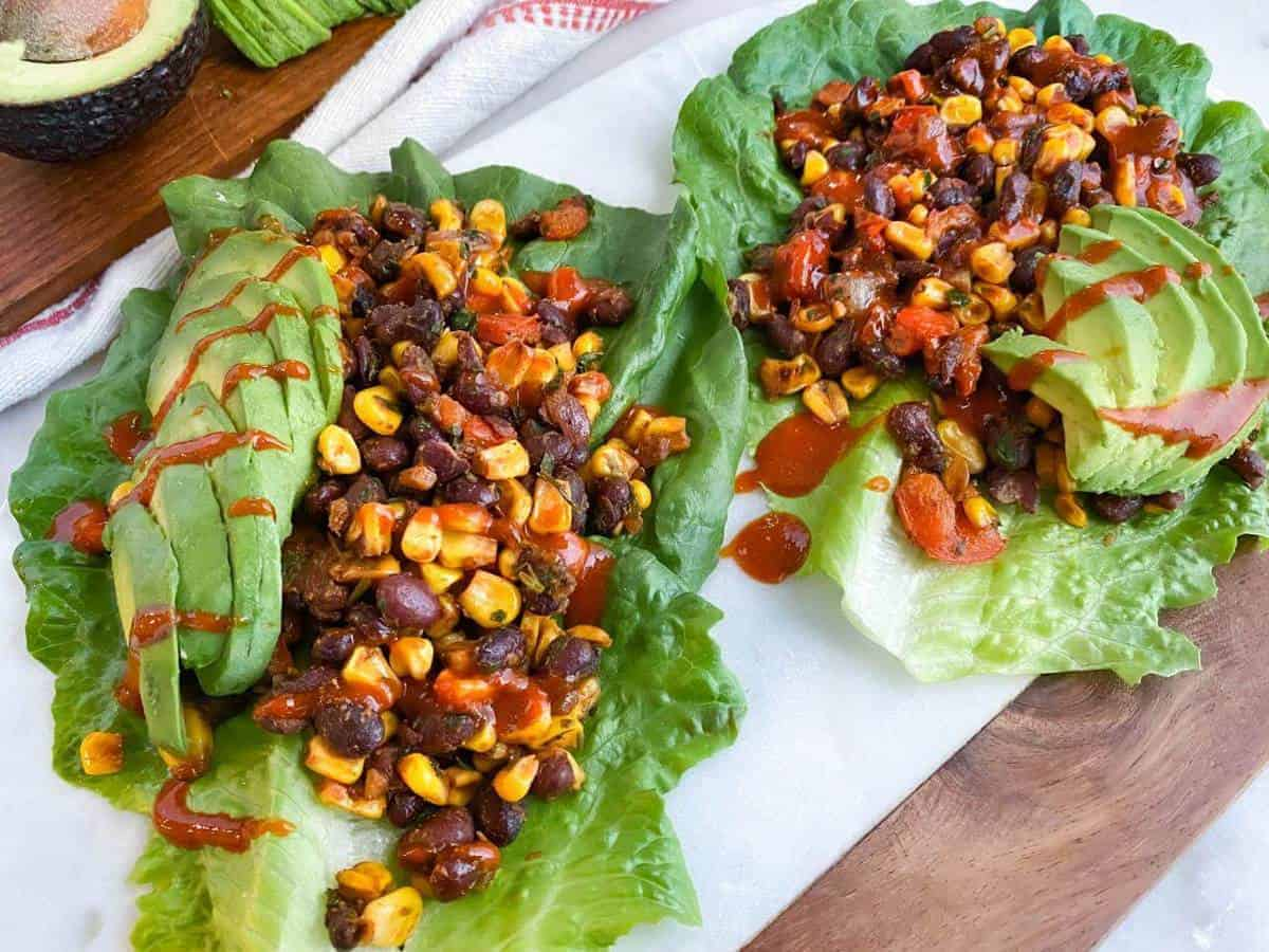 Two lettuce wraps filled with a mix of beans and corn and topped with sliced avocado and hot sauce