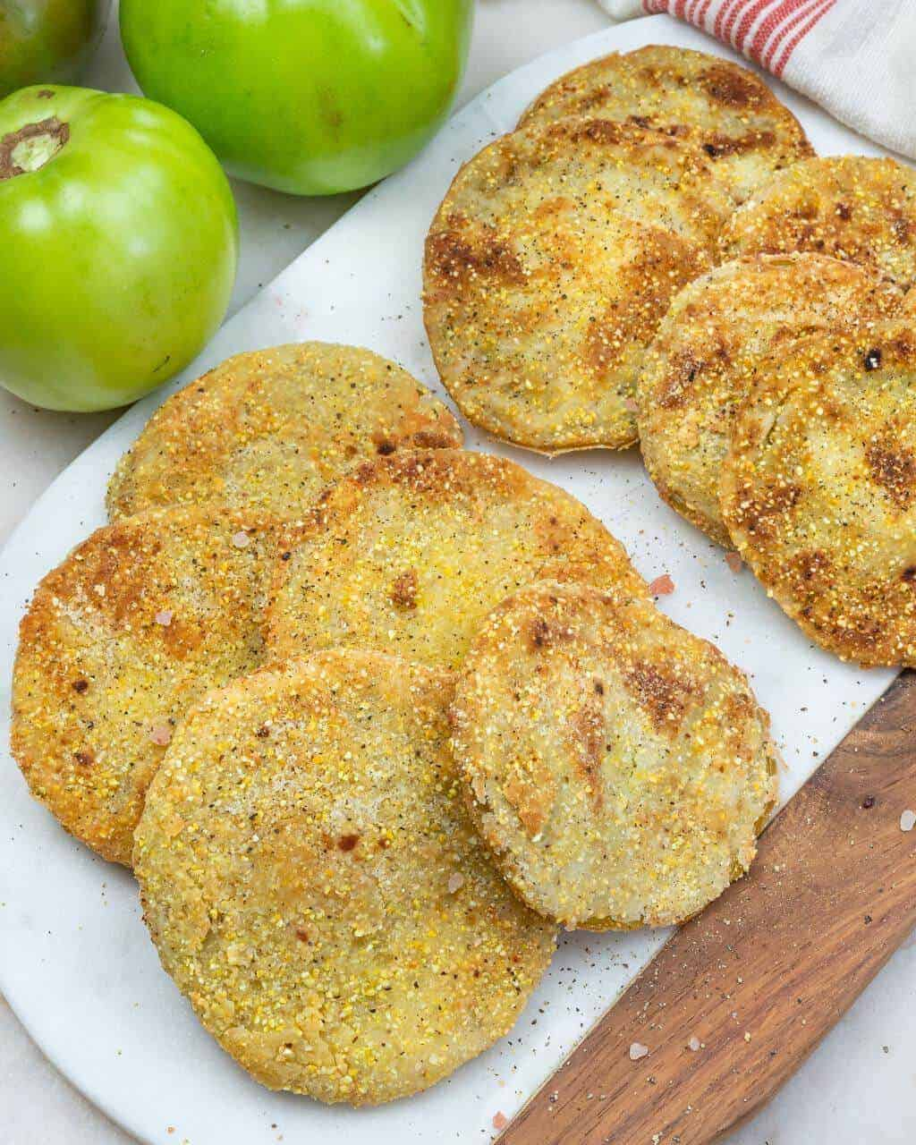 stack of fried green tomatoes on a white background with green whole tomatoes in the background
