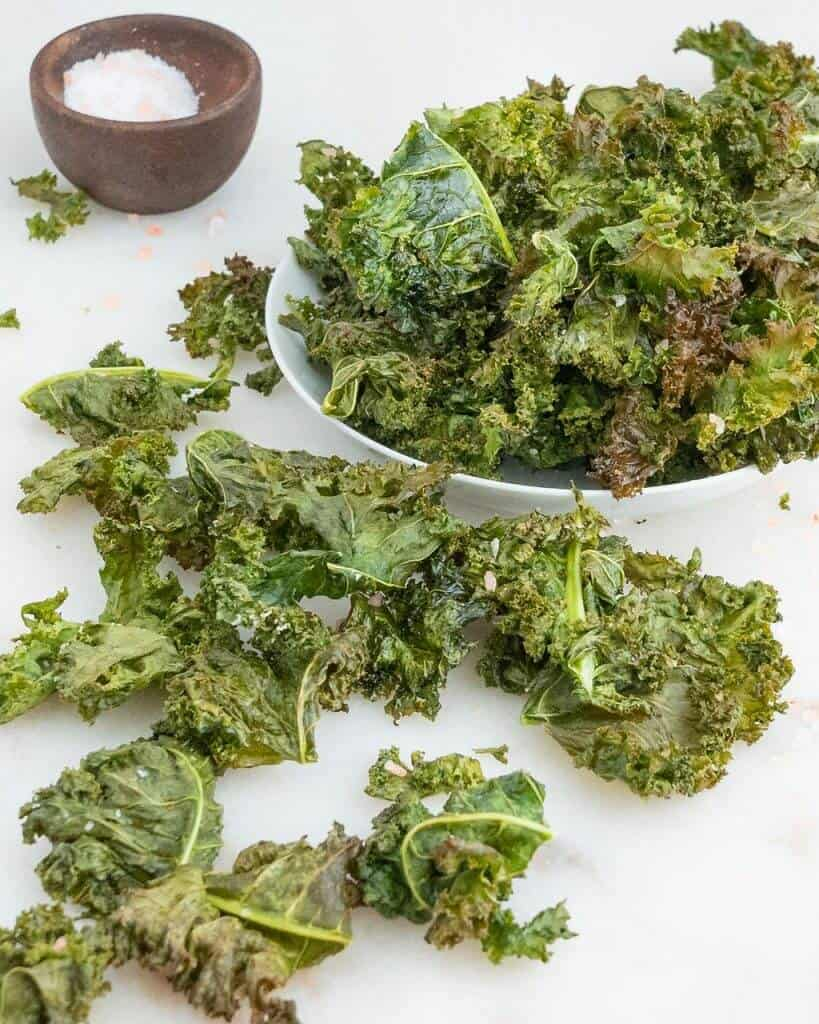 finished kale chips spread out against a white background