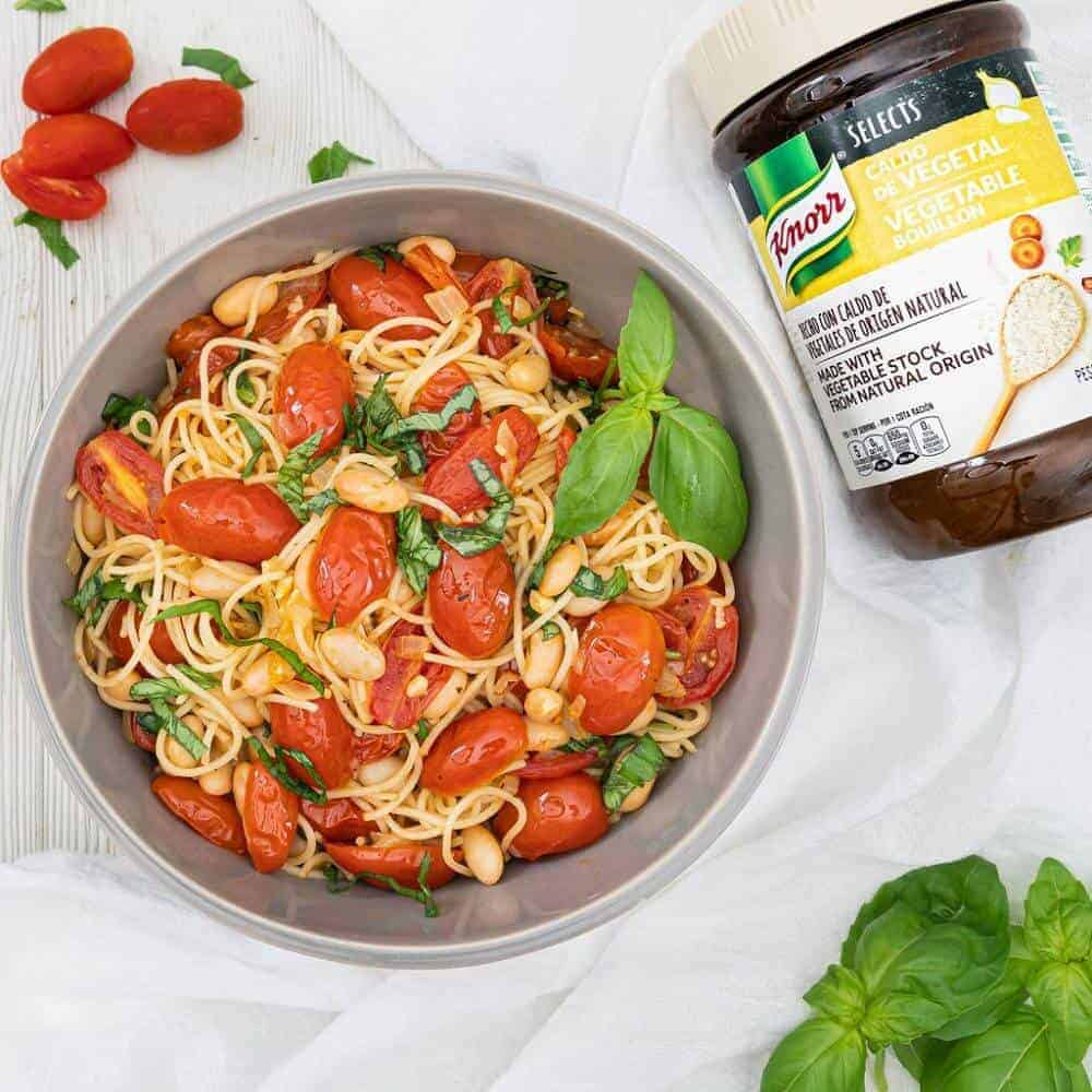 finished Tomato Basil Pasta in a gray bowl with product and ingredients against a white background