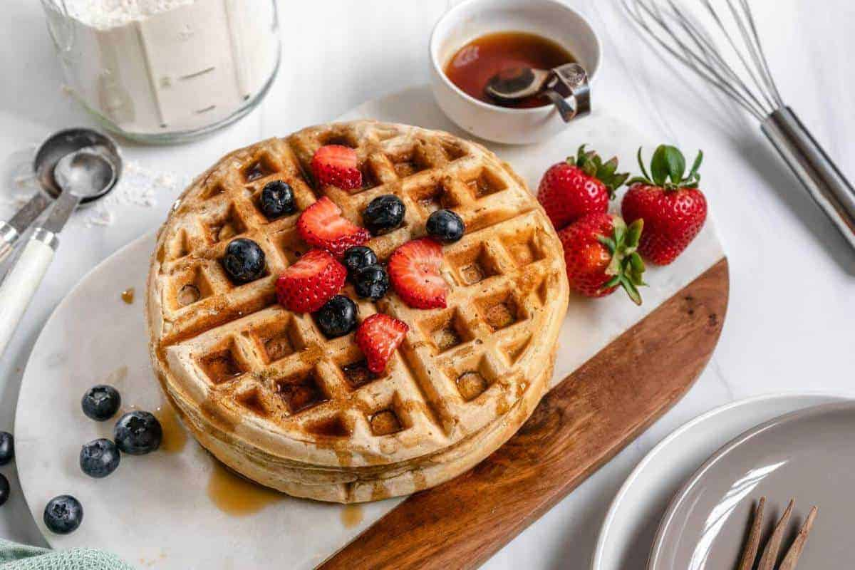 Two vegan waffles stacked on top of each other with berries and syrup on top.