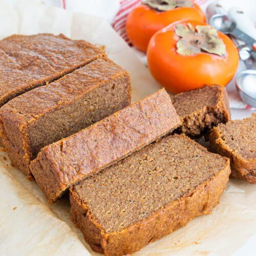 persimmon bread slices on a white surface with persimmons in the background