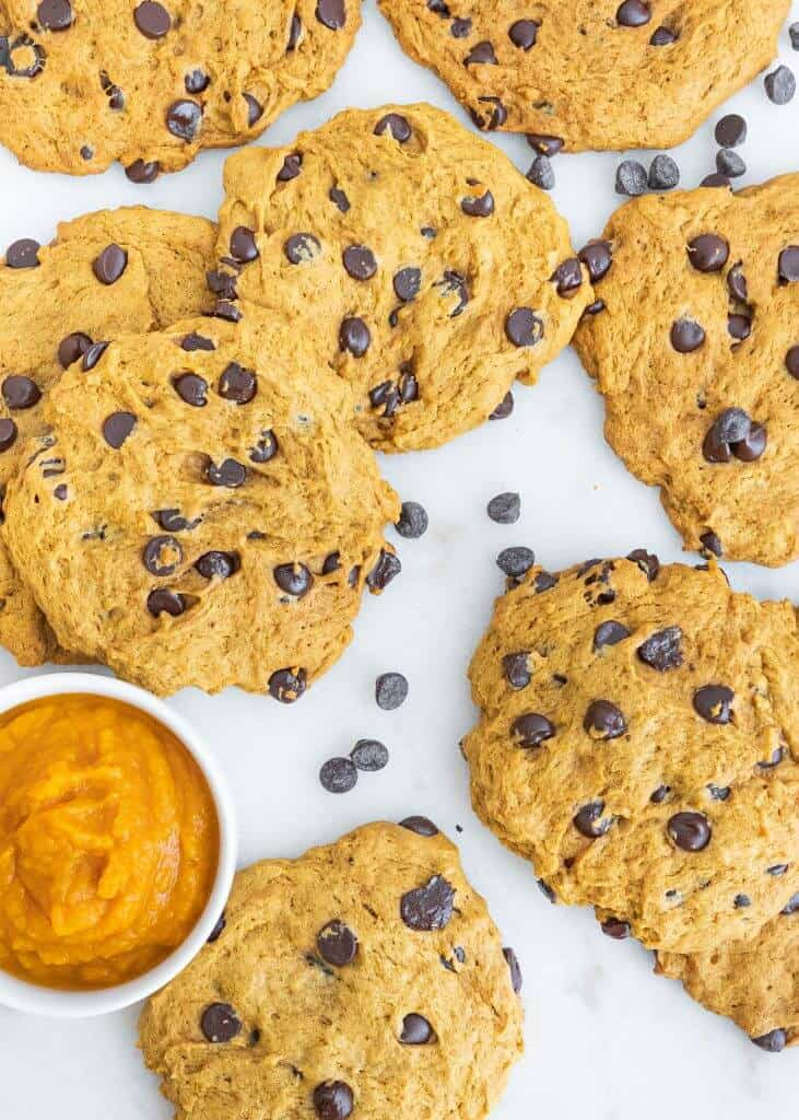 several finished pumpkin chocolate chip cookies scattered on a white surface