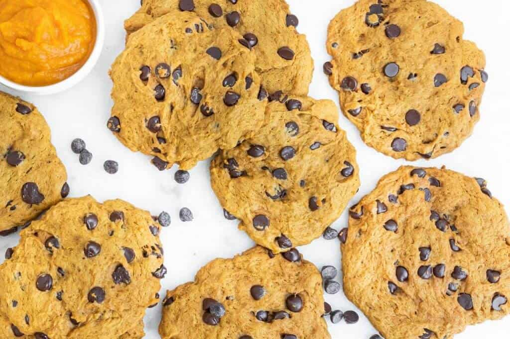 several finished pumpkin chocolate chip cookies on a white background
