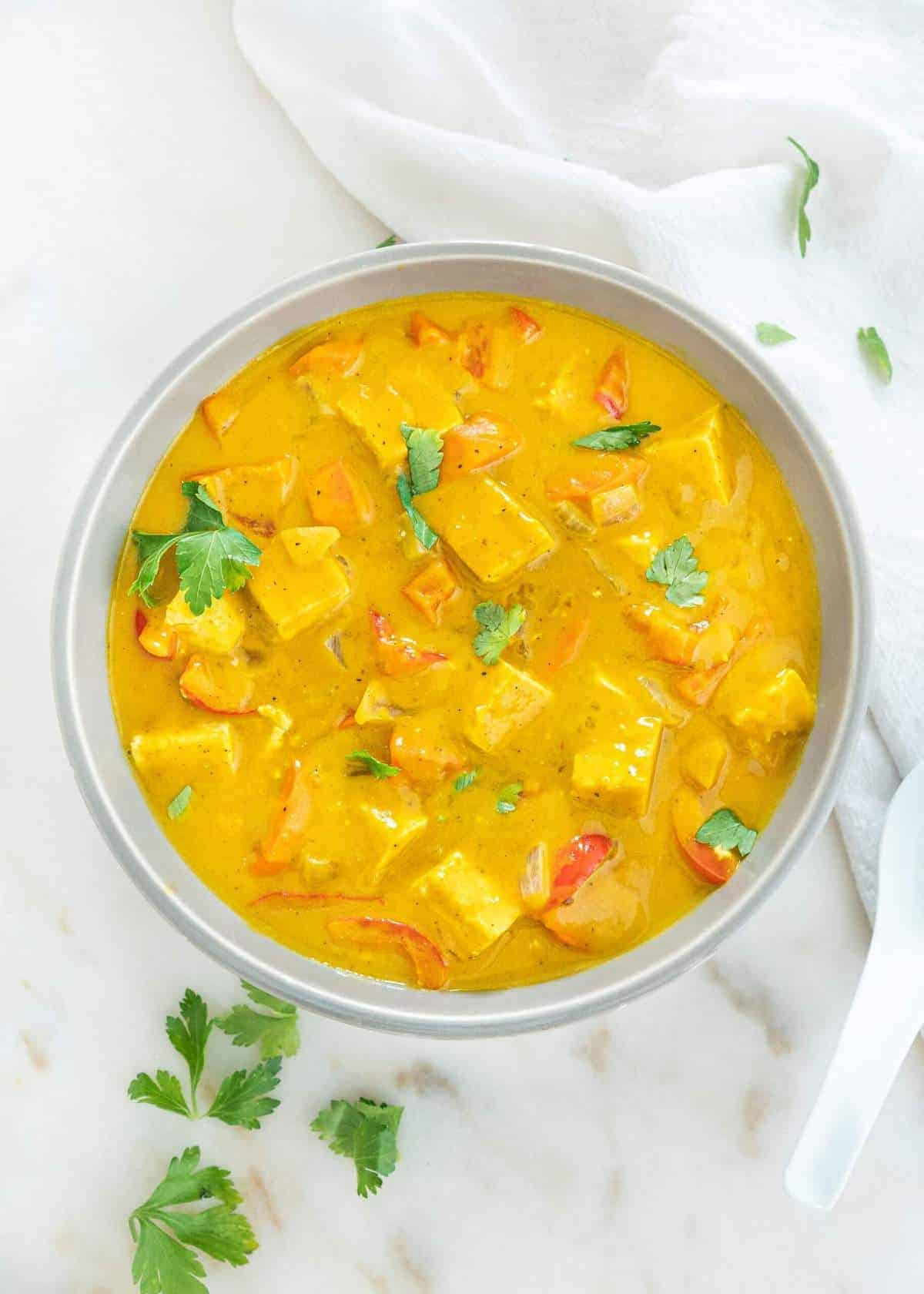 finished bowl of pumpkin curry against a white marble background