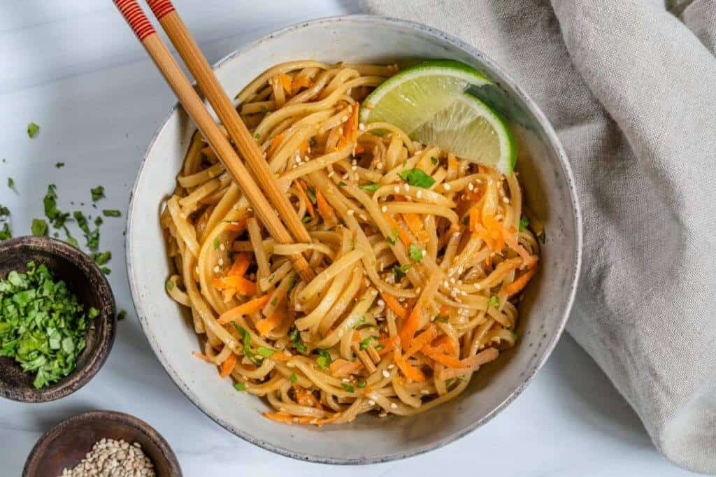 finished Sesame Noodle Salad plated in a white dish with chopsticks against a white background