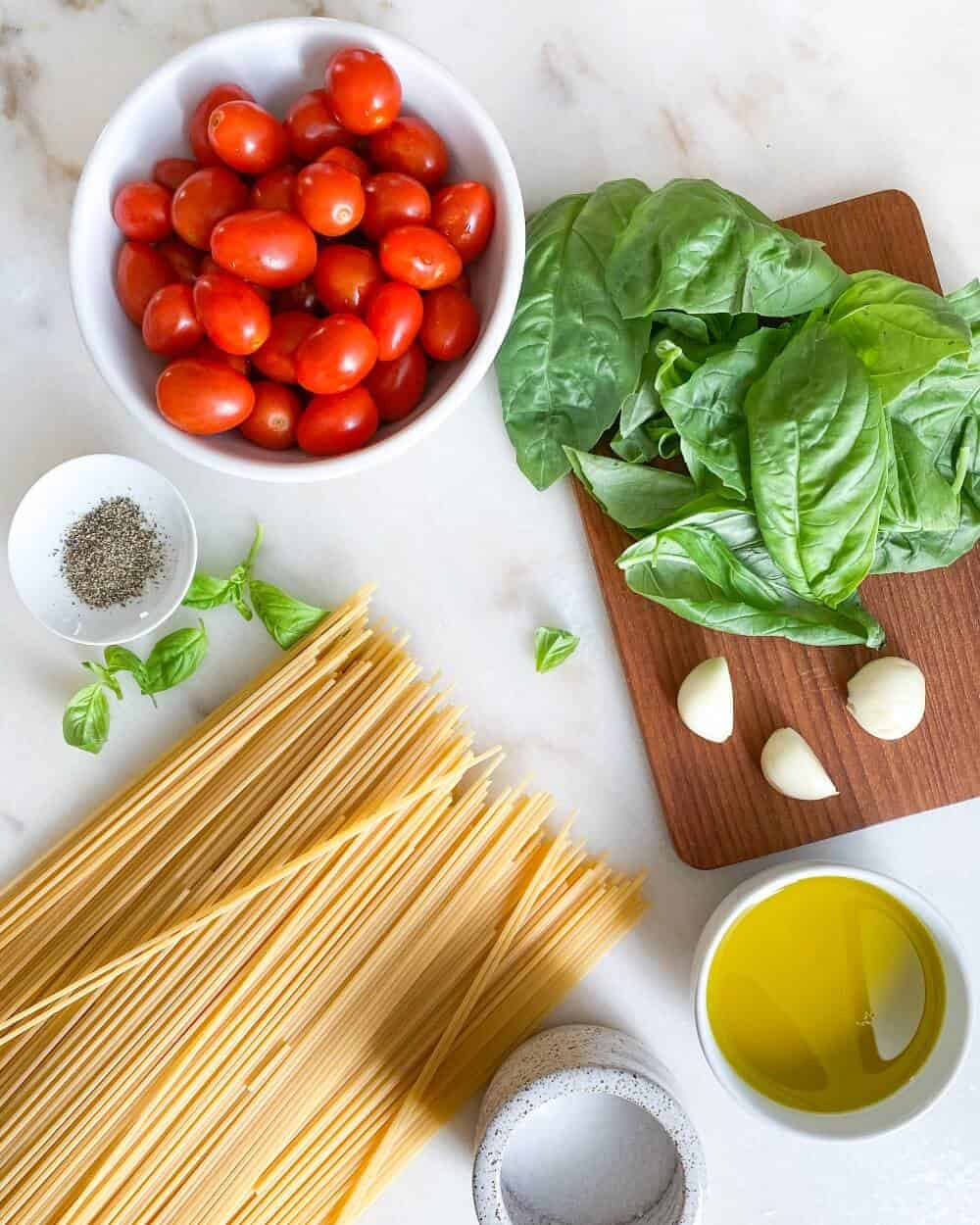 Ingredients of tomato and basil pasta displayed on a counter